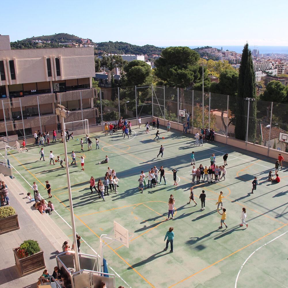 Vista aèria del pati de l'escola amb les vistes de Barcelona de fons